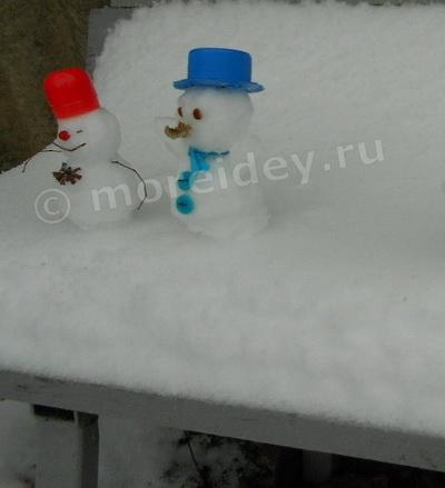 Маленькие смешные снеговики на лавочке