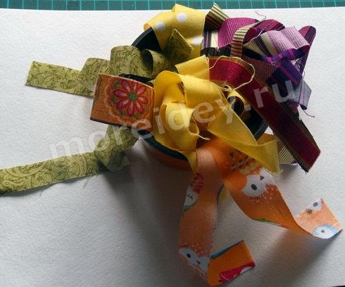 Поделка - подвеска с плетенным из полосок ткани цветком